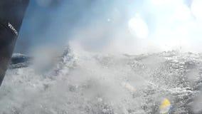 Ψεκάζοντας και καταβρέχοντας αφρός με το νερό από κάτω από τη λέμβο ταχύτητας στην πλάτη απόθεμα βίντεο