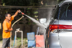 Ψεκάζοντας πλυντήριο πίεσης ατόμων για το πλύσιμο αυτοκινήτων στο κατάστημα προσοχής αυτοκινήτων Focu Στοκ Εικόνες