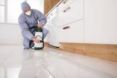 Ψεκάζοντας φυτοφάρμακο εξολοθρευτών στην κουζίνα στοκ φωτογραφία με δικαίωμα ελεύθερης χρήσης