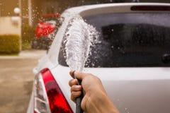 Ψεκάστε με το νερό για να πλύνετε το αυτοκίνητο με το χέρι στοκ φωτογραφίες