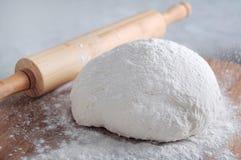 Ψεκάστε το αλεύρι στην ακατέργαστη ζύμη ψωμιού κοντά στο ξύλινο κύλισμα Στοκ εικόνες με δικαίωμα ελεύθερης χρήσης