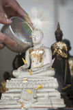 Ψεκάστε το νερό επάνω σε μια εικόνα του Βούδα, υπόβαθρο εποχής Στοκ Εικόνες