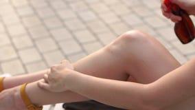 Ψεκασμοί γυναικών sunscreen ποδιών στο πετρέλαιο πρίν μαυρίζει απόθεμα βίντεο