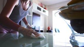 Ψεκασμός νοικοκυρών καθαριστικός και σκούπισμα ενός πίνακα γυαλιού απόθεμα βίντεο