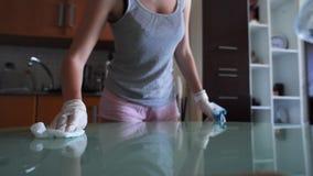 Ψεκασμός νοικοκυρών καθαριστικός και σκούπισμα ενός πίνακα γυαλιού φιλμ μικρού μήκους