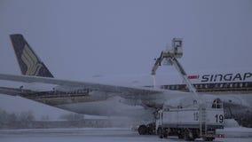 Ψεκασμός του αποψύχοντας ρευστού στο αεροπλάνο της Singapore Airlines το χιονώδες βράδυ φιλμ μικρού μήκους