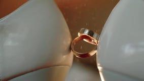 Ψεκασμός του δαχτυλιδιού αρραβώνων αρωμάτων που τοποθετείται - μεταξύ των γαμήλιων παπουτσιών νυφών κλείστε επάνω Σε αργή κίνηση  φιλμ μικρού μήκους