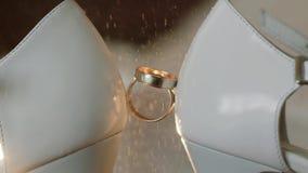 Ψεκασμός του δαχτυλιδιού αρραβώνων αρωμάτων που τοποθετείται - μεταξύ των γαμήλιων παπουτσιών νυφών κλείστε επάνω Μακροεντολή σε  φιλμ μικρού μήκους