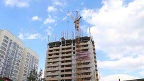 Ψηλές εργασίες γερανών στο εργοτάξιο οικοδομής με το κατοικημένο κτήριο στο καλοκαίρι φιλμ μικρού μήκους