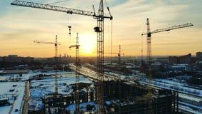 Ψηλοί γερανοί στο εργοτάξιο οικοδομής στο ηλιοβασίλεμα απόθεμα βίντεο
