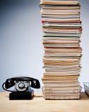 Ψηλός σωρός των αρχείων και της γραφικής εργασίας στο γραφείο με το τηλέφωνο στοκ φωτογραφία με δικαίωμα ελεύθερης χρήσης