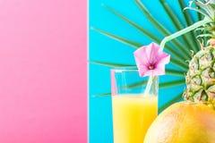 Ψηλό γυαλί με τον πρόσφατα συμπιεσμένο ανανά χυμό φρούτων εσπεριδοειδών τροπικό με το άχυρο και το λουλούδι Φούξια ρόδινο μπλε υπ Στοκ φωτογραφίες με δικαίωμα ελεύθερης χρήσης