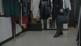 Ψηλό μοντέρνο αρσενικό πρότυπο που φορά το μαύρο παλτό που περπατά σε ένα κατάστημα που ψωνίζει στην αναζήτηση των εξαρτημάτων ιμ απόθεμα βίντεο