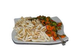 Ψημένα δαχτυλίδια καλαμαριών με μια σαλάτα των καρότων, των κρεμμυδιών, του άνηθου και του μαϊντανού Στοκ Φωτογραφία