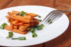 Ψημένα καρότα με τα πράσινα κρεμμύδια σε ένα άσπρο πιάτο Στοκ εικόνες με δικαίωμα ελεύθερης χρήσης