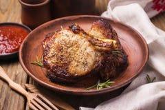 Ψημένα κομμάτια του χοιρινού κρέατος σε ένα πιάτο αργίλου Στοκ Εικόνες