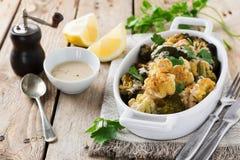 Ψημένα κουνουπίδι και μπρόκολο με μια σάλτσα του tahini σε ένα άσπρο κεραμικό πιάτο Στοκ Φωτογραφίες