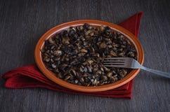 Ψημένα μανιτάρια στο πιάτο, ξύλινο υπόβαθρο Στοκ Εικόνες