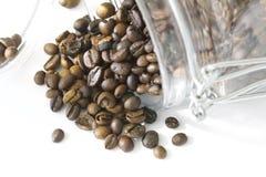 Ψημένα μαύρα φασόλια καφέ που ανατρέπονται από ένα βάζο Στοκ Εικόνες