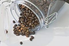 Ψημένα μαύρα φασόλια καφέ που ανατρέπονται από ένα βάζο Στοκ εικόνα με δικαίωμα ελεύθερης χρήσης