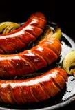 Ψημένα λουκάνικα με το κρεμμύδι προσθηκών και χορτάρια στο τηγάνι Στοκ Φωτογραφίες