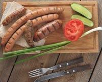 Ψημένα λουκάνικα σε μια σχάρα στο ξύλινο υπόβαθρο Στοκ φωτογραφία με δικαίωμα ελεύθερης χρήσης