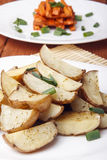 Ψημένα πατάτες και καρότα με τα πράσινα κρεμμύδια σε ένα άσπρο πιάτο Στοκ Φωτογραφίες