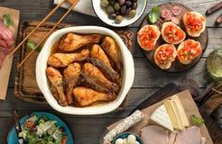 Ψημένα πόδια κοτόπουλου με την ποικιλία των πρόχειρων φαγητών στον ξύλινο πίνακα Στοκ Φωτογραφίες
