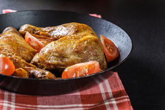 Ψημένα πόδια κοτόπουλου με τις σφήνες και τις ντομάτες πατατών Στοκ φωτογραφία με δικαίωμα ελεύθερης χρήσης