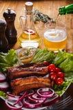 Ψημένα πλευρά χοιρινού κρέατος με τα λαχανικά και τη μουστάρδα και χύνοντας μπύρα από ένα μπουκάλι σε ένα γυαλί Στοκ φωτογραφίες με δικαίωμα ελεύθερης χρήσης