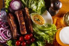 Ψημένα πλευρά χοιρινού κρέατος με τα λαχανικά, τη μουστάρδα και ένα ποτήρι της μπύρας σε έναν ξύλινο πίνακα Στοκ Εικόνες