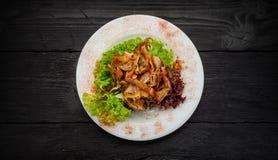 Ψημένα στη σχάρα αυτιά χοιρινού κρέατος σε ένα άσπρο πιάτο πέρα από το σκοτεινό ξύλινο υπόβαθρο Πρόχειρο φαγητό μπύρας Στοκ Φωτογραφία