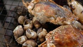 Ψημένα στη σχάρα γαρίδες, οστρακόδερμα και καβούρι στα κάγκελα σομπών, μαγειρεύοντας θαλασσινά σχαρών απόθεμα βίντεο
