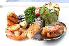 Ψημένα στη σχάρα θαλασσινά με τα ψημένα λαχανικά στο άσπρο πιάτο Στοκ εικόνες με δικαίωμα ελεύθερης χρήσης