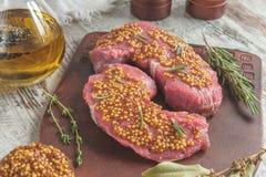 Ψημένα στη σχάρα κομμάτια βόειου κρέατος σε μια τέμνουσα ελιά πινάκων με τα μαριναρισμένα χορτάρια μουστάρδας, δεντρολιβάνου και  Στοκ Φωτογραφίες