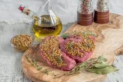 Ψημένα στη σχάρα κομμάτια βόειου κρέατος σε μια τέμνουσα ελιά πινάκων με τα μαριναρισμένα χορτάρια μουστάρδας, δεντρολιβάνου και  Στοκ Φωτογραφία
