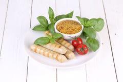 Ψημένα στη σχάρα λουκάνικα με την ντομάτα, τη μουστάρδα και το βασιλικό σε ένα άσπρο ξύλινο υπόβαθρο Στοκ Εικόνες