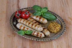 Ψημένα στη σχάρα λουκάνικα με τις ντομάτες, τη μουστάρδα και το βασιλικό σε ένα ξύλινο υπόβαθρο Στοκ Εικόνα