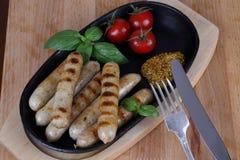 Ψημένα στη σχάρα λουκάνικα με τις ντομάτες, τη μουστάρδα και το βασιλικό σε ένα ξύλινο υπόβαθρο Στοκ εικόνα με δικαίωμα ελεύθερης χρήσης