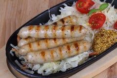 Ψημένα στη σχάρα λουκάνικα με τις ντομάτες, τη μουστάρδα και το βασιλικό σε ένα ξύλινο υπόβαθρο Στοκ εικόνες με δικαίωμα ελεύθερης χρήσης