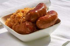 Ψημένα στη σχάρα λουκάνικα, πατάτες και sauerkraut σε ένα άσπρο πιάτο Στοκ εικόνα με δικαίωμα ελεύθερης χρήσης