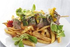 Ψημένα στη σχάρα οβελίδια και λαχανικά κρέατος με τις τηγανιτές πατάτες Στοκ φωτογραφία με δικαίωμα ελεύθερης χρήσης