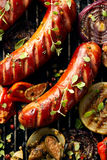 Ψημένα στη σχάρα λουκάνικα και λαχανικά με τα καρυκεύματα προσθηκών και φρέσκα χορτάρια σε μια σχάρα Στοκ εικόνες με δικαίωμα ελεύθερης χρήσης