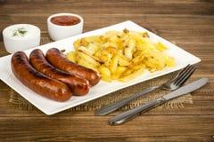 Ψημένα στη σχάρα λουκάνικα και τηγανισμένες πατάτες στο άσπρο πιάτο στην αγροτική ξύλινη επιφάνεια Στοκ Εικόνα