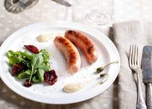 Ψημένα στη σχάρα λουκάνικα με τη σαλάτα σε ένα άσπρο πιάτο Στοκ εικόνες με δικαίωμα ελεύθερης χρήσης