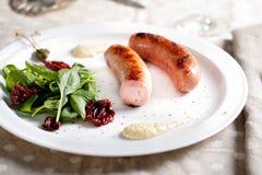 Ψημένα στη σχάρα λουκάνικα με τη σαλάτα σε ένα άσπρο πιάτο Στοκ φωτογραφία με δικαίωμα ελεύθερης χρήσης
