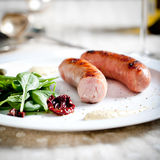 Ψημένα στη σχάρα λουκάνικα με τη σαλάτα σε ένα άσπρο πιάτο Στοκ Φωτογραφία