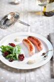 Ψημένα στη σχάρα λουκάνικα με τη σαλάτα σε ένα άσπρο πιάτο Στοκ Εικόνες