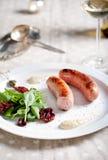 Ψημένα στη σχάρα λουκάνικα με τη σαλάτα σε ένα άσπρο πιάτο Στοκ Φωτογραφίες