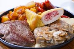 Ψημένα στη σχάρα λουκάνικα με τις πατάτες, τα μανιτάρια και το ψημένο κοτόπουλο σε ένα τηγάνι σχαρών στοκ εικόνα